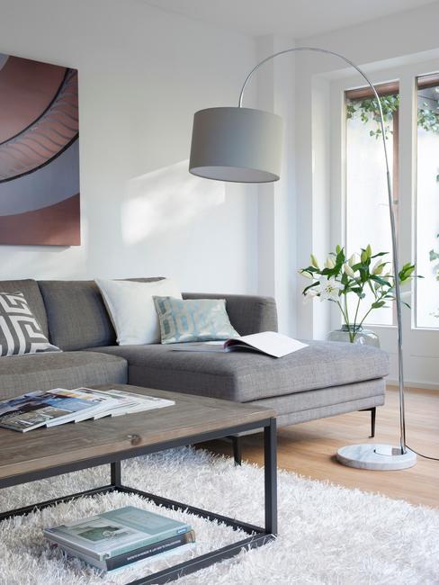Szary salon z kanapą narożą, dużą, stojącą lampą oraz stolikiem kawowym