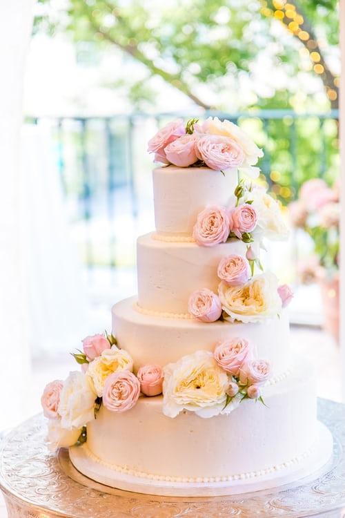 Biały tort weselny udekorowany peonami