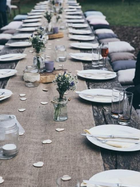 Zastawiony stół weselny w stylu rustykalnym z drobnymi dekoracjami w kształcie serca