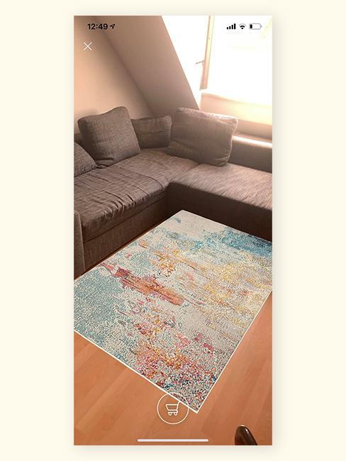 Zdjęcie pokoju z szarą, narożną kanapą i dywanem z AR