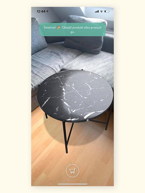 Szara sofa w salonie w aplikacji z rozszerzoną rzeczywistością z czarnym stolikiem kawowym