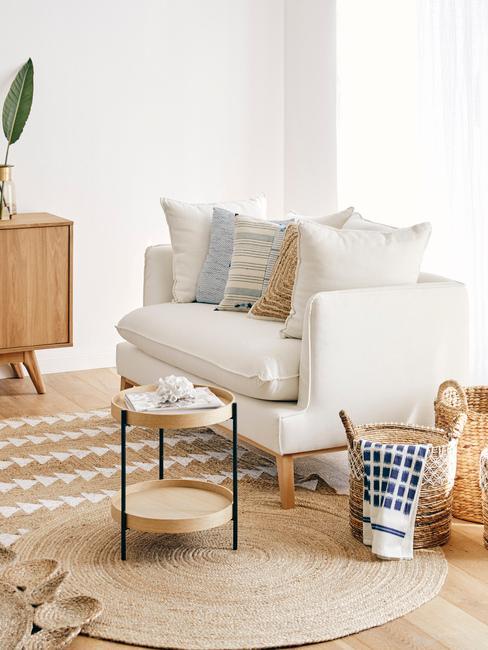 Biały salon w stylu boho z jasną sofą, drewnianym stoliczkiem oraz koszykami