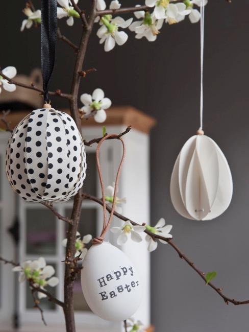 Dekoracyjne pisanki w białym kolorze wiszące na drzewie