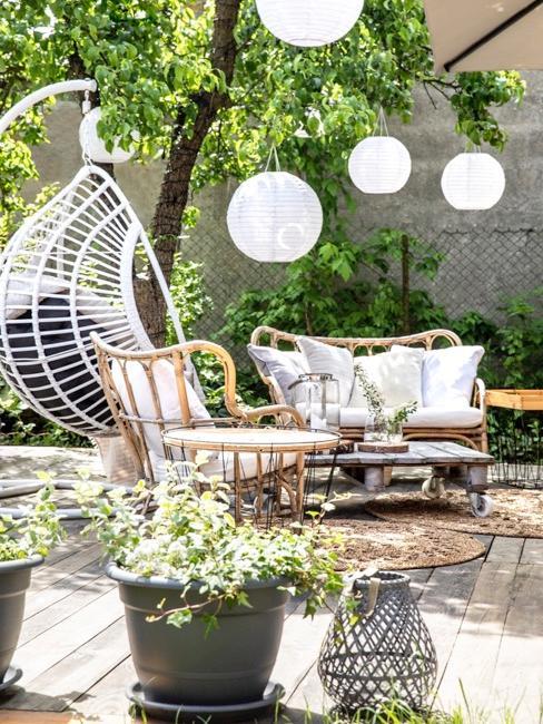Taras z szarymi kwietnikami, fotelem wiszącym i kompletem ogrodowym