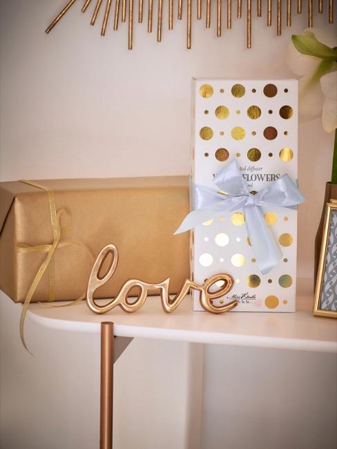 Elegancko opakowane prostokątne prezenty położone na stoliku wraz z napisem love