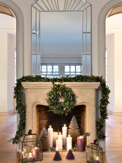 Kominek udekorowany świąteczną girlandą z jodły i świecami