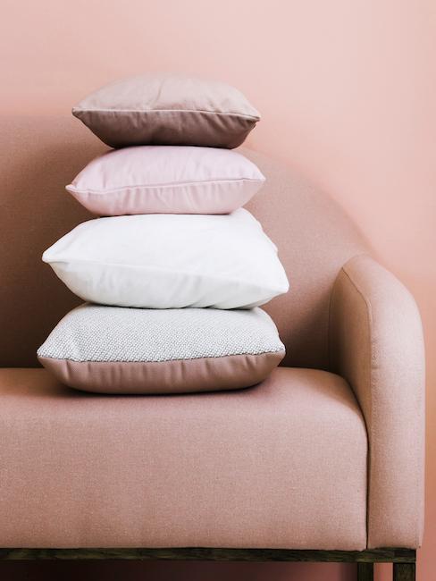 Poduszki w odcieniach bieli i różu ułożone piętrowo na k
