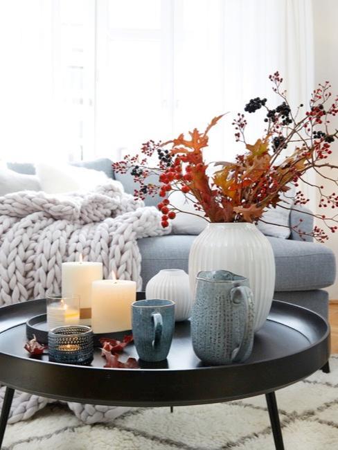 Jesienna dekoracja na stoliku kawowym w salonie z gałązkami i jagodami.