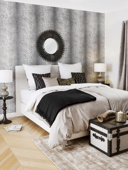 Sypialnia z tapetą w cętki, lustrem w kształcie słońca i łóżkiem kontynentalnym