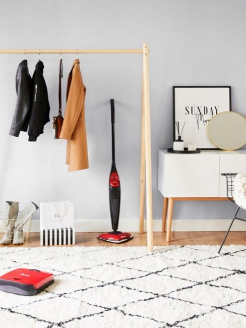 burro con ropa, un tocador blanco, una alfombra blanca y una aspiradora
