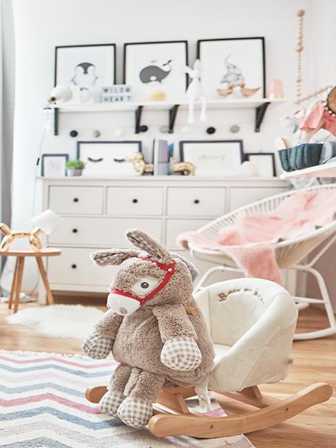 Pokój dziecięcy dla dziewczynki z kolorowym dywanem, białą komodą, dekoracjami oraz obrazkami na ścianie
