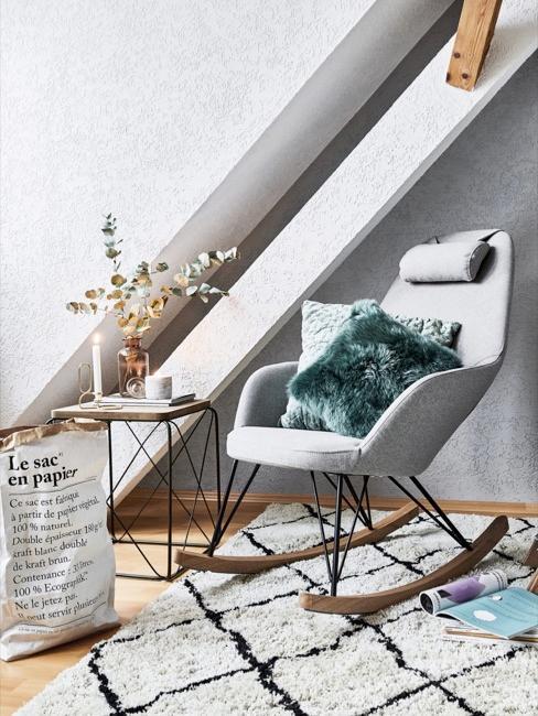 Angolo lettura vicino a finestra con poltrona grigia e cuscino turchese