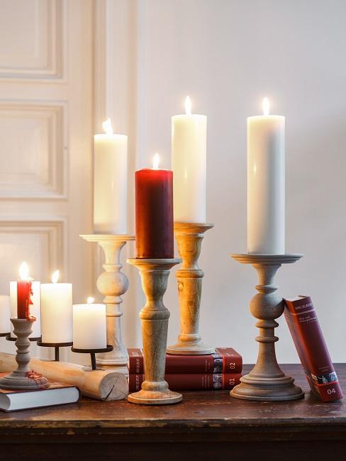 Liczne świece w świecznikach stojące na drewnianej komodzie