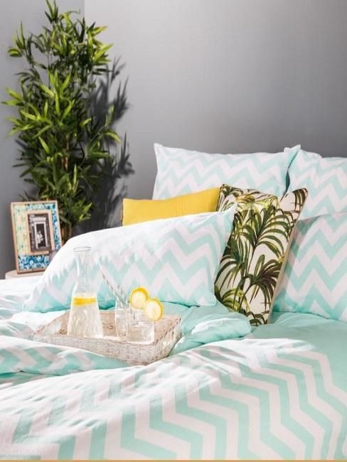 Łóżko przed szarą ścianą, w narożniku roślina i ramka i kolorowa pościel