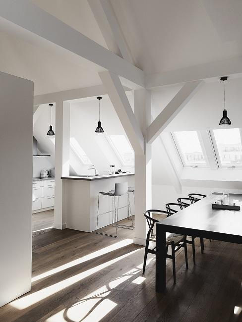 Offene Wohnküche in Weiß mit schwarzen Möbeln und Lampen im Essbereich