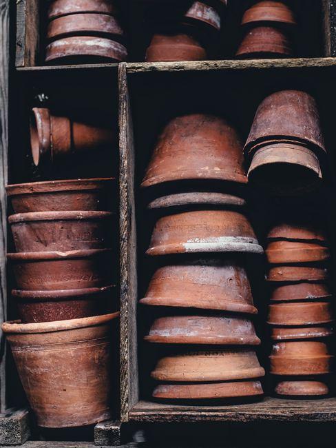 Macetas de terracota apiladas en estantes