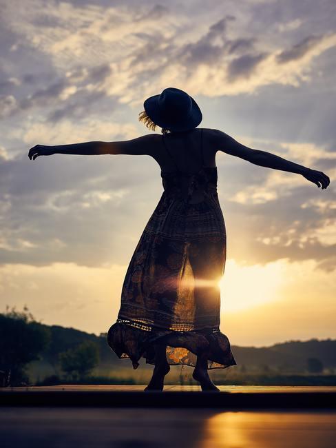 Puesta de sol detrás de una chica con un vestido y brazos abiertos