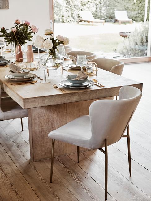 Jadalnia z drewnianym stołem, jasnymi krzesłami oraz dekoracjami stołu: zastawą oraz kwiatami