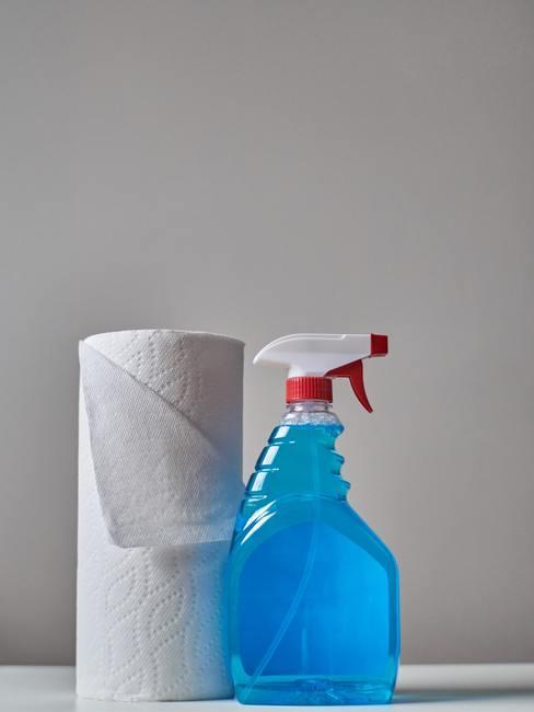 Niebieski płyn do mycia stojący obok rolki ręcznika papierowego
