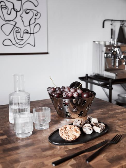 Zbliżenie na drewniany stół z owocami i szklaną karafką