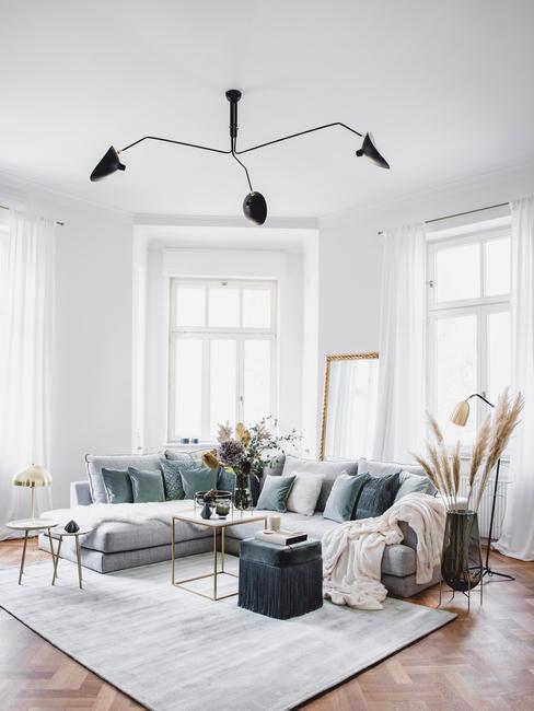 Jasny salon, na środku sofa z ozdobnymi poduszkami, jasny dywan