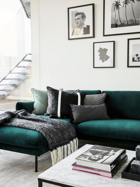 Szmaragdowa sofa, marmurowy stolik i czarno-białe fotografie