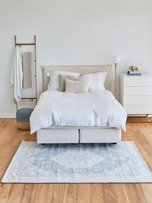 Sypialnia z drewniana podłogą, podwójnym łóżkiem, dywanem oraz białą komodą