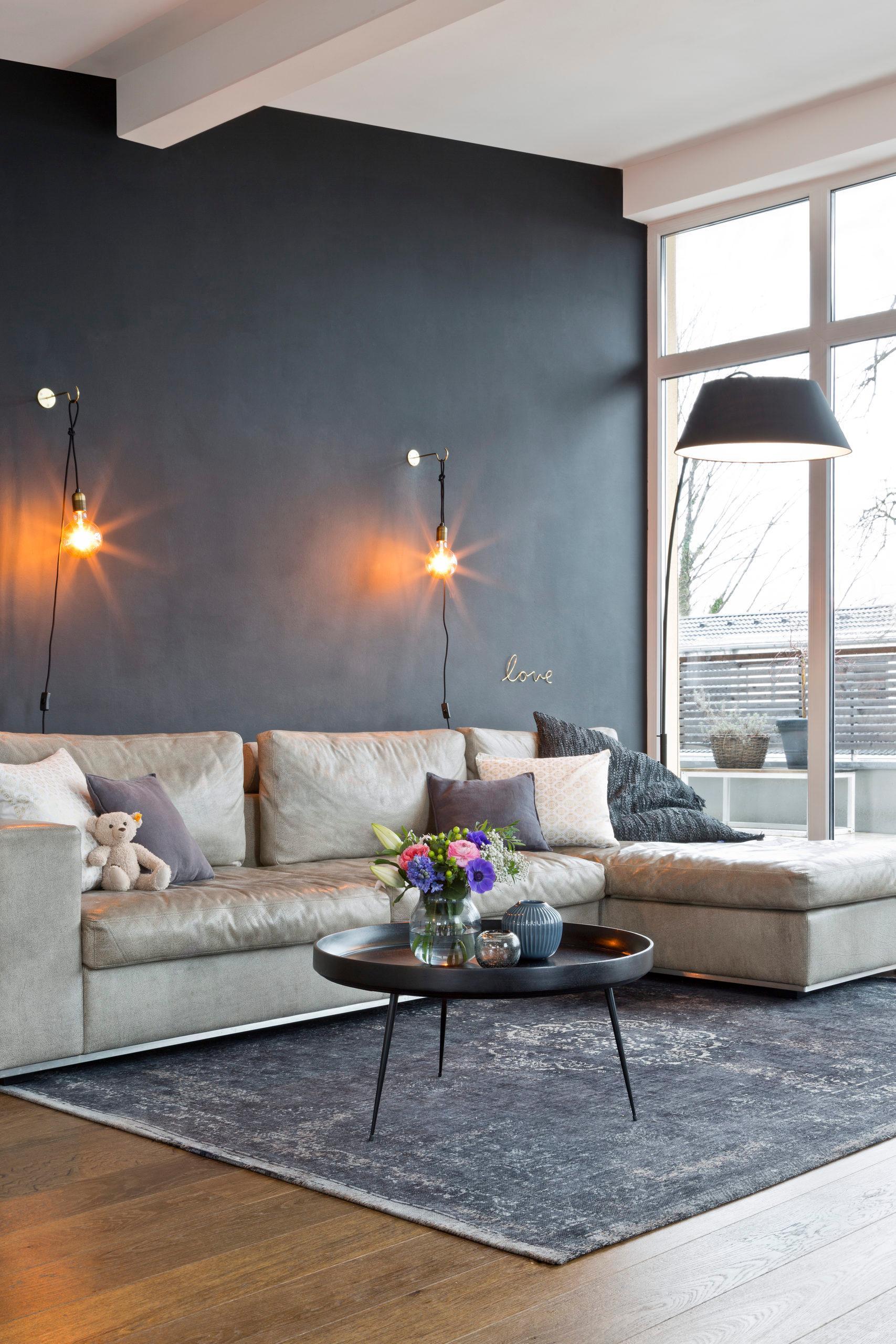 Narożna, kremowa sofa w salonie o ciemnych ścianach