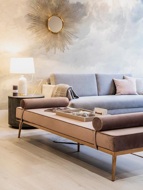 Betonowa ściana w salonie z szarą kanapą i metalową dekoracją