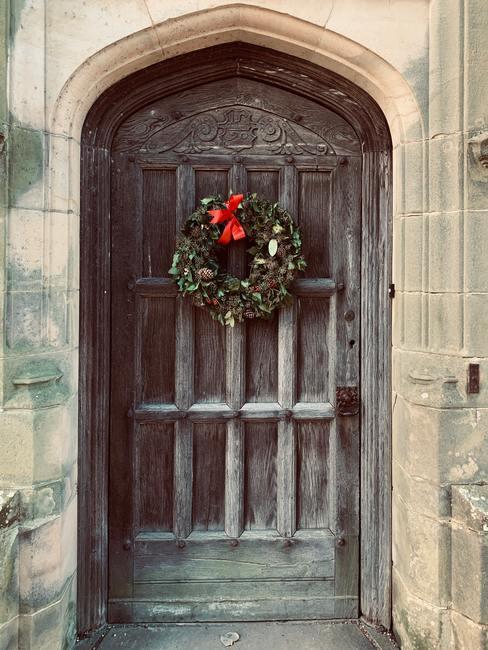 Świąteczny wianek z jodłowych gałązek i szyszek z czerwoną kokardą