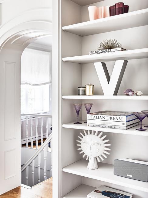 Biała sypialnia z wysoką szafką, na której są ustawione książki, dekoracje oraz ozdobna litera