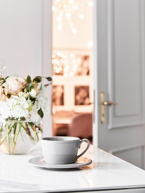 Fliżanka i kwiaty na jasnym blacie w kuchni