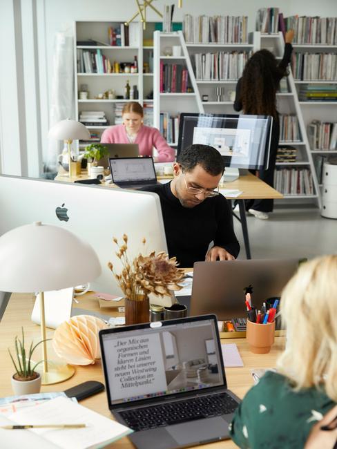Biuro małej firmy w której są 4 osoby siedziące przy biurkach