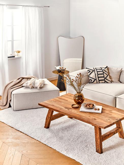 Fragment jasnego salonu z drewnianym stolikiem kawowym, dużym pufem oraz kremową kanapą i lustrem