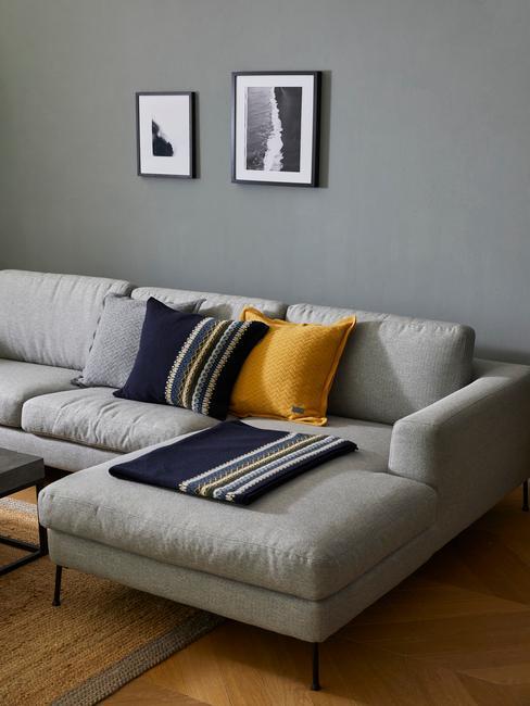 Szary salon w stylu skandynawskim z arożną sofą, poduszkami oraz dekoracjami na ścianie