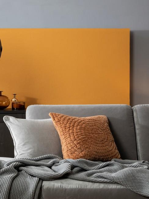 Salon z pomarańczową ścianą i szarą sofą