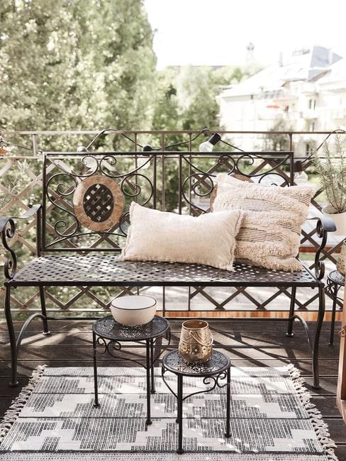 Mały balkon w bloku z metalową ławką, stolikami ogrodowymi oraz roślinami w doniczkach