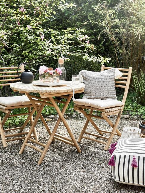 Dwa krzesła oraz stolik wykonane z drewna ustawione w ogrodzie przed domem