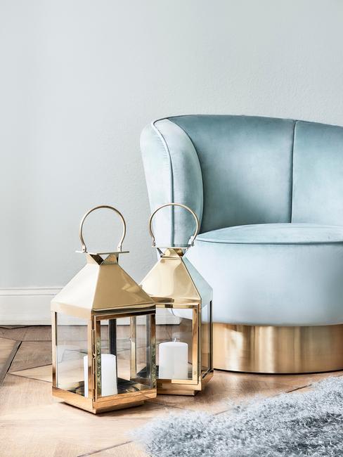 Turkusowy fotel oraz złote latarenki w salonie
