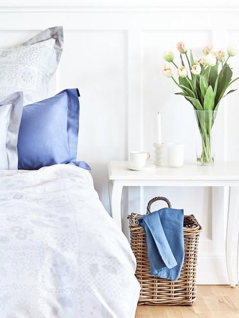 Sypialnia w stylu rustykalnym z biłyśmy ścianami oraz meblami, wazonem kwiatów i szarą pościelą