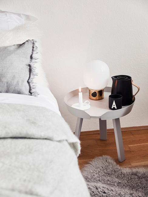 Sypialnia z łóżkiem, na którym jest szary koc oraz poduszka, małym stolikiem nocnym z czajnikiem oraz kubkiem