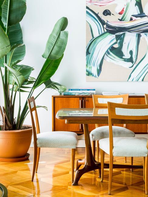 Jasny salon z retro krzesłami oraz stołem, nowoczesnym obrazem oraz dużą rośliną
