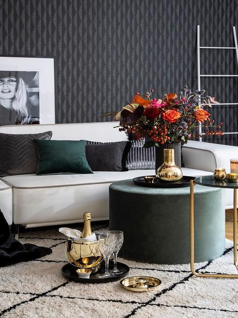 Salon z tapetą na ścianie, jasną sofą, aksamitnym pusem z wazonem kwiatów oraz małym stolikiem pomocniczym