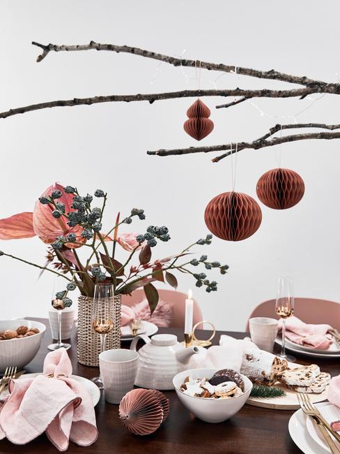 Zastawiony stół w pomieszczeniu z zastawą oraz wazonem z kwiatami oraz wiszącą gałęzią z ręcznie robionymi bombkami choinkowymi