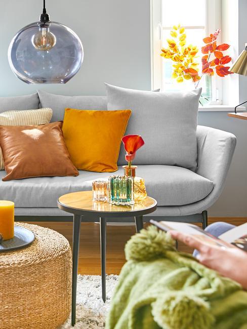 Salon z szarą sofą, stolikiem kawowym, pufem, kolorowymi poduszkami oraz wazonem z liści na parapacie