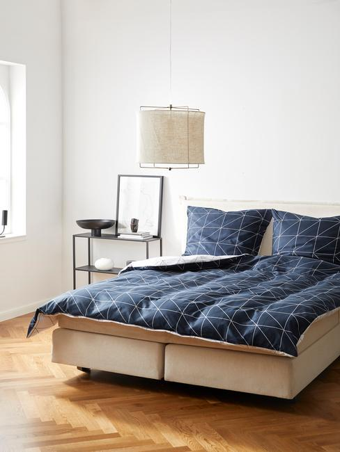 Minimalistyczna sypialnia z niebieska posciela oraz otwarta półka
