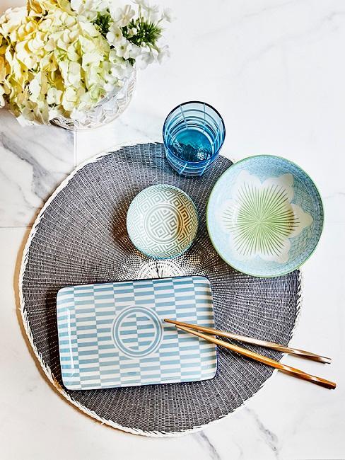 Asiatische Tischdeko in Blau und Grün auf Tisch mit Essstäbchen neben Pflanze