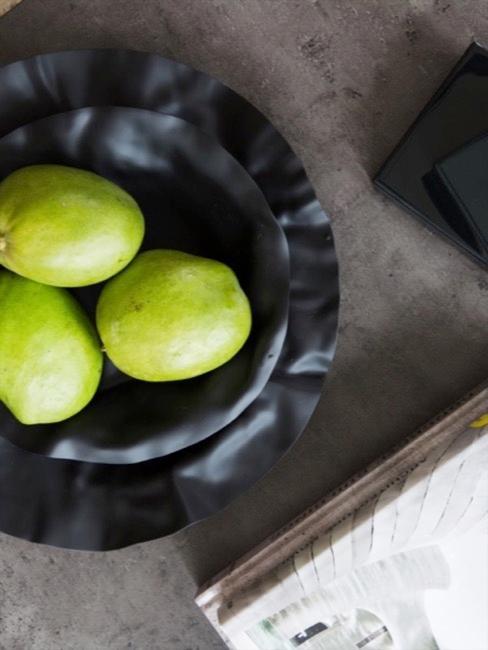 Zbliżenie na czarna tacę z owocami na blacie z betonu