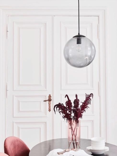 Czarny okrągły stół z kulistą szklaną lampą wiszącą i czerwonym szklanym wazonem z suszkami