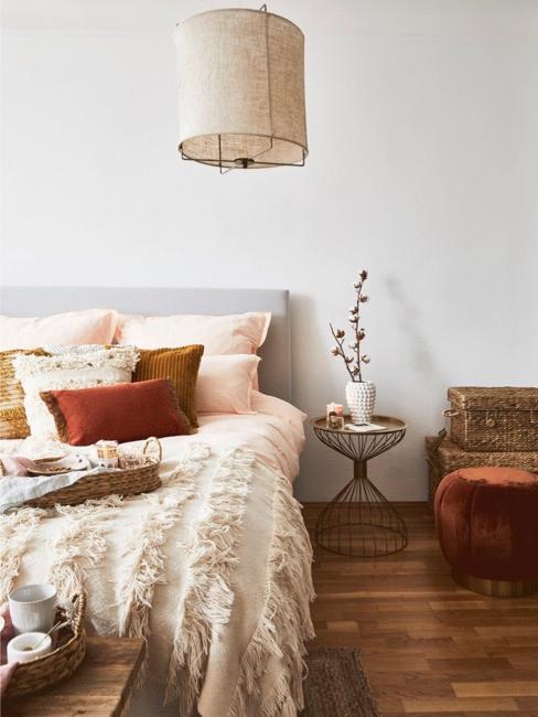 Slaapkamer in bohemian style interieur met veel kussens op bed